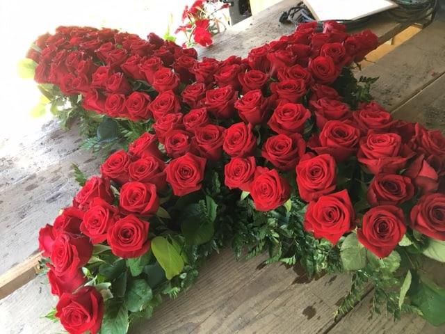 Croix réalisée tout en roses rouge pour un deuil